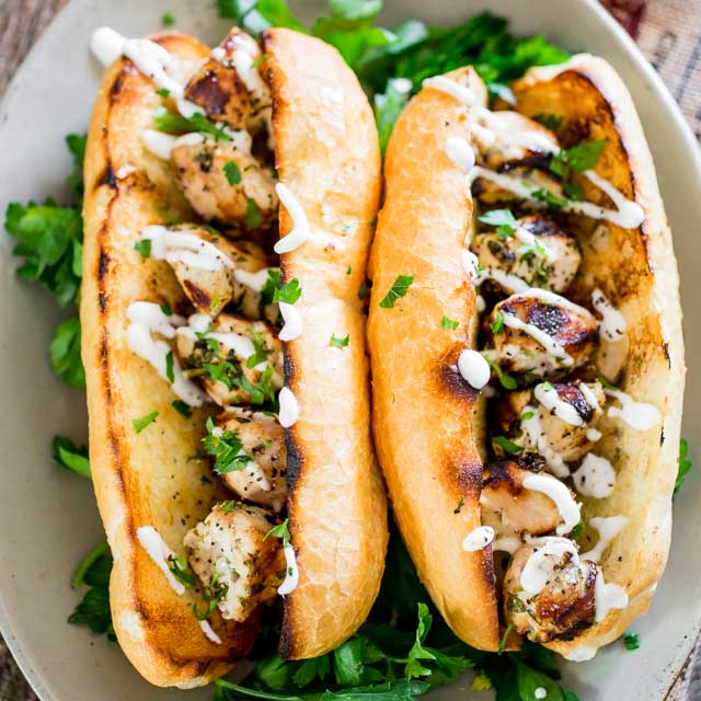 These chicken spiedies are marinated in a lemon, olive oil and herb marinade, grilled and served over Italian rolls, then drizzled with a delicious garlic sauce. Simple, quick and undeniably delicious.