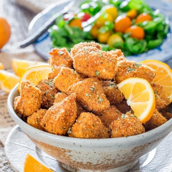 a bowl full of chicken milanese bites garnished with orange wedges