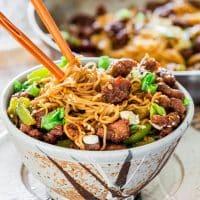 chopsticks stuck in a bowl full of mongolian beef ramen noodles