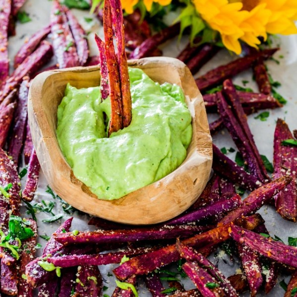 a bowl of avocado aioli surrounded by purple yams