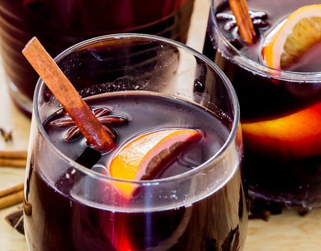 two glasses of mulled wine with oranges and cinnamon sticks
