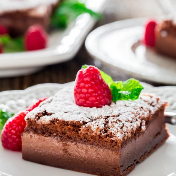 a slice nutella magic cake dusted with powdered sugar and topped with a fresh raspberry on a plate