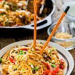 a plate full of spicy thai chicken and veggie noodles with chopsticks stuck in it