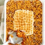overhead shot of sweet potato casserole with a piece missing, a serving spoon resting in the empty space