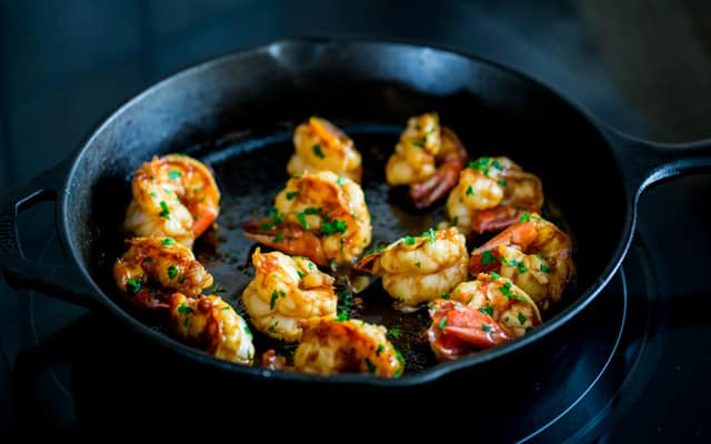 Honey Soy Shrimp cooked and sitting in a cast iron skillet topped with parsley