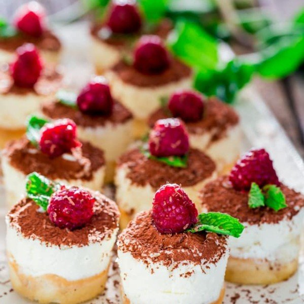 mini tiramisu cheesecakes topped with raspberries on a plate