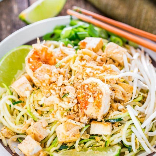 a plate of pad thai zoodles garnished with lime wedges