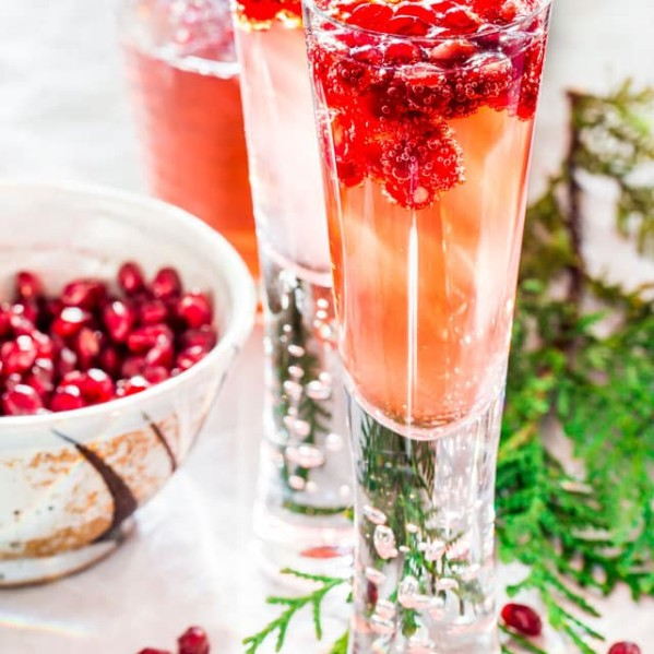 sparkling pomegranate elderflower cocktails with pomegranate floating in it
