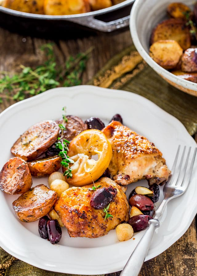Skillet Braised Greek Chicken Thighs on a plate with potatoes, lemon, olives, and garlic.