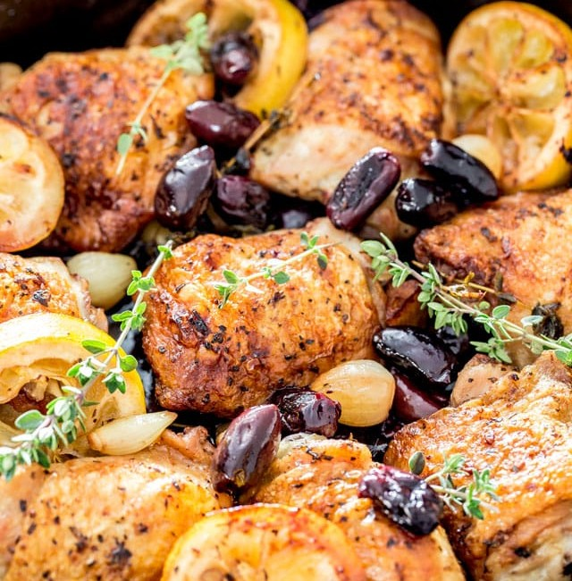 a pot of braised greek chicken thighs, kalamata olives and lemon slices