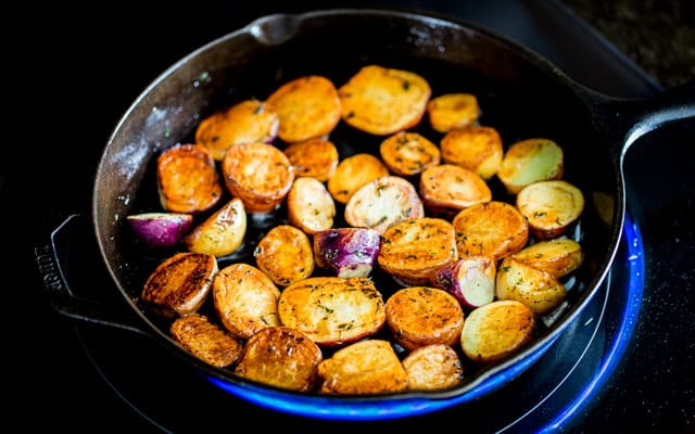 Skillet Potatoes cut in half and browned on a stove top