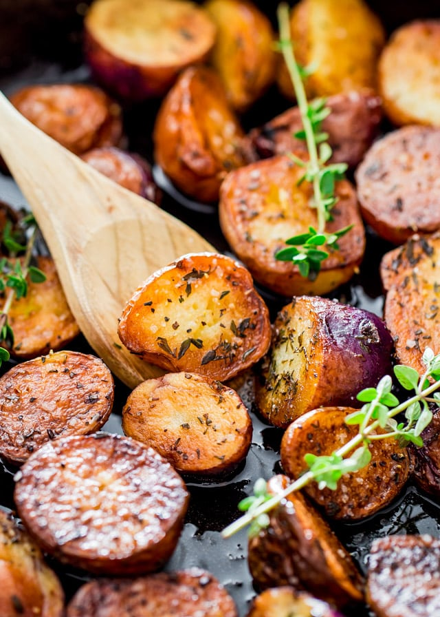 crisp Skillet Potatoes with a wooden spoon and two sprigs of thyme