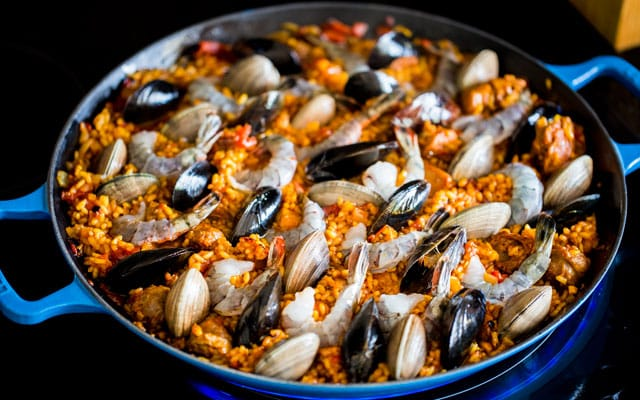 Chicken and Seafood Paella cooking on the stove with prawns, muscles, and clams