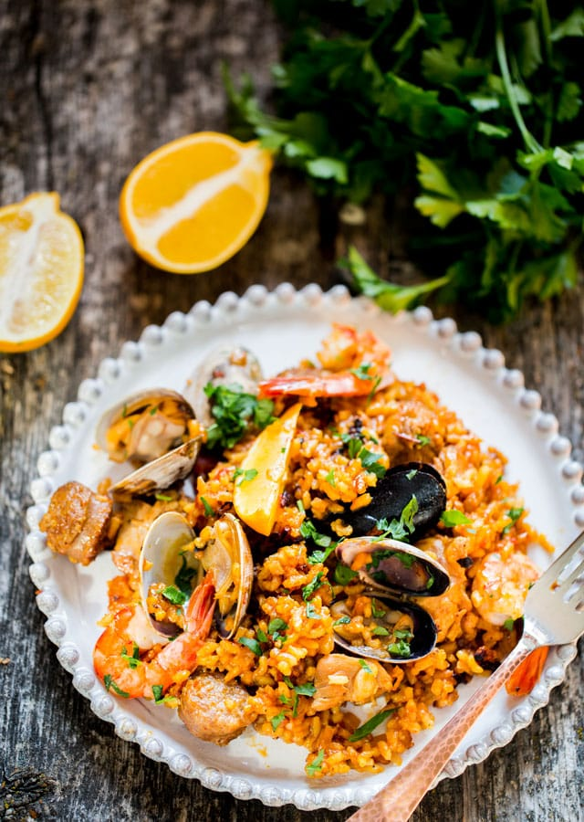 overhead of a plate filled with Chicken and Seafood Paella and a lemon cut in half