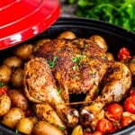 side view shot of Moroccan chicken in a pot with potatoes tomatoes and garlic