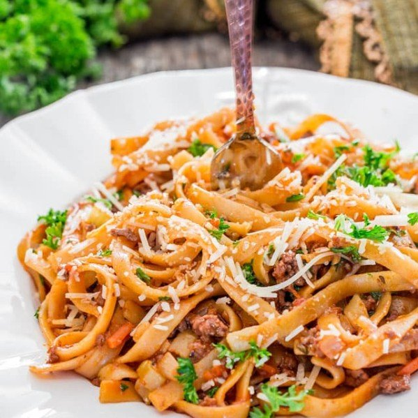 a fork twirling the fettuccine with beef ragu on a plate