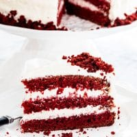 side view shot of a piece of red velvet cake on a plate