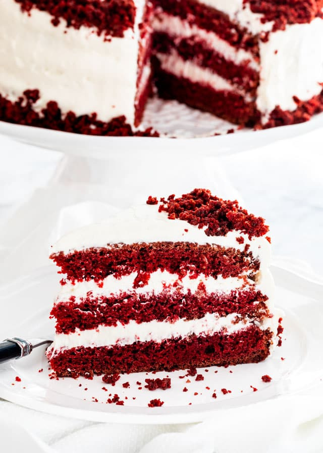 A slice of Red Velvet Cake on a white plate with the rest of the cake on a cake stand in the background