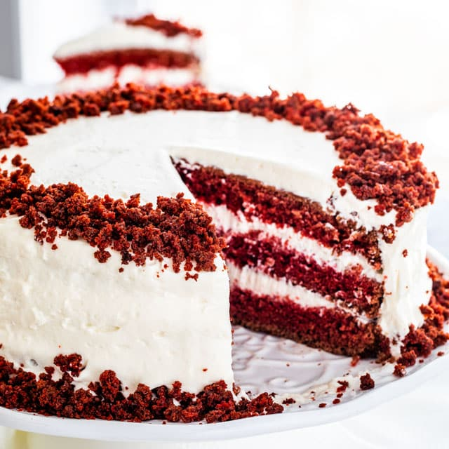 red velvet cake on a white platter with a slice taken out of it