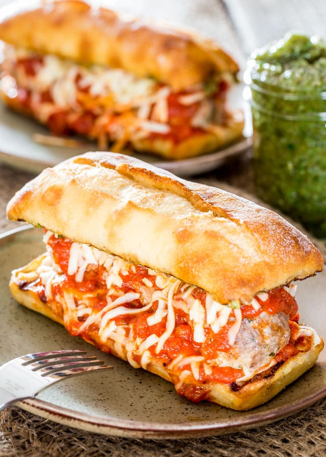 The Godfather Meatball Sub - the ultimate meatball sub with giant meatballs, smothered in sauce and cheese, in a toasted ciabatta bun with pesto sauce. A meatball sub worthy of The Godfather!