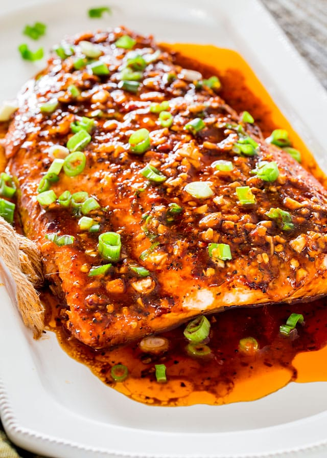 firecracker baked salmon on a platter topped with chopped green onion