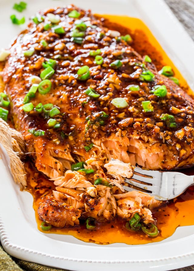firecracker baked salmon on a a white platter with a fork topped with chopped green onion