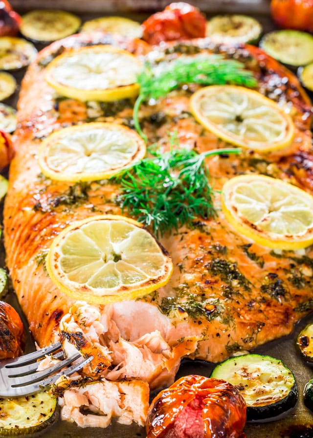 Salmon and Veggies Sheet Pan Dinner with a fork, lemon wedges, and fresh dill