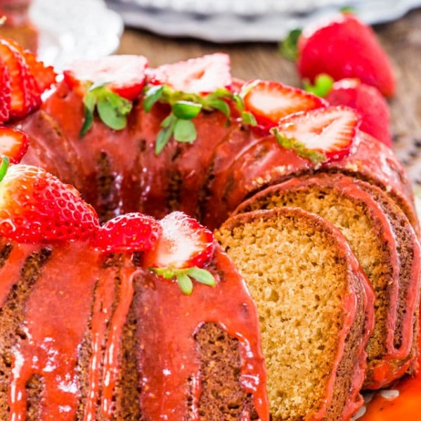 side view shot of a sliced pound cake with strawberry glaze