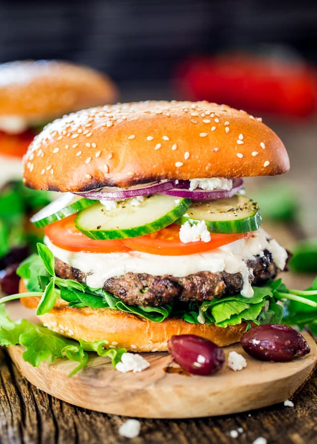 a greek lamb burger on a wooden plate with 2 kalamata olives