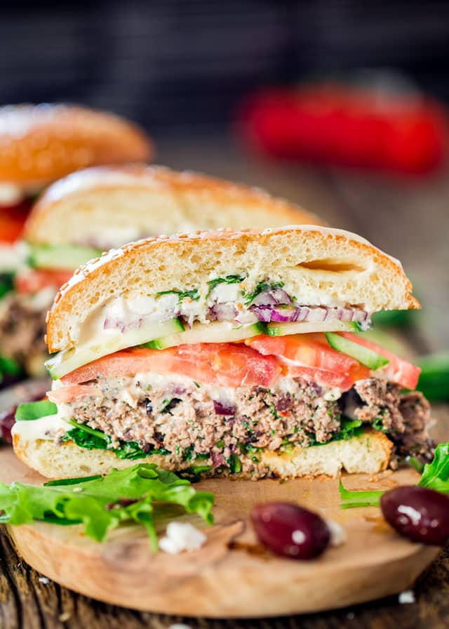 a greek lamb burger cut in half on a wooden plate with 2 kalamata olives