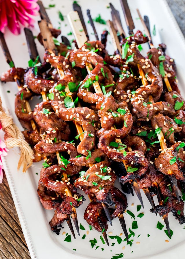 overhead of Beef Teriyaki Skewers piled on a white platter