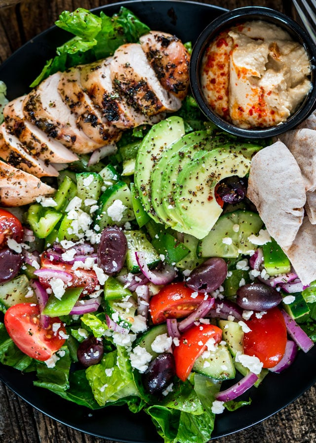 overhead of a plate of Mediterranean Grilled Chicken Salad with a side of hummus