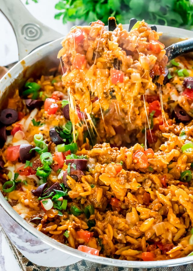 a spoon lifting a big cheesy scoop of taco orzo out of a pot
