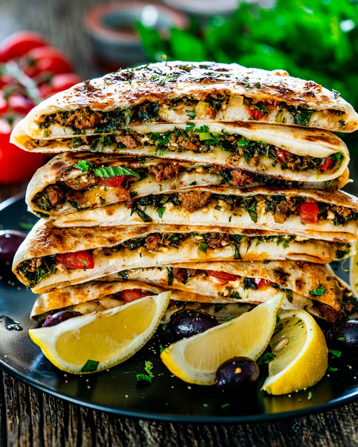 a stack of turkish gozleme with lamb on a black plate garnished with lemon slices