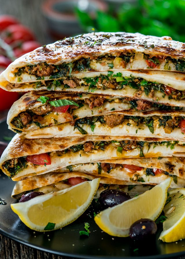 a stack of Turkish Gozleme with Lamb on a plate with 3 lemon wedges
