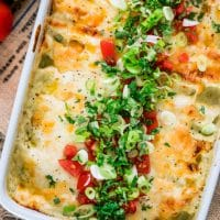 overhead shot of the green chile chicken enchilada casserole in a baking dish topped with diced tomato and green onion