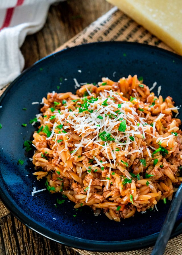 spicy pork ragu on a blue plate with parmesan and parsley