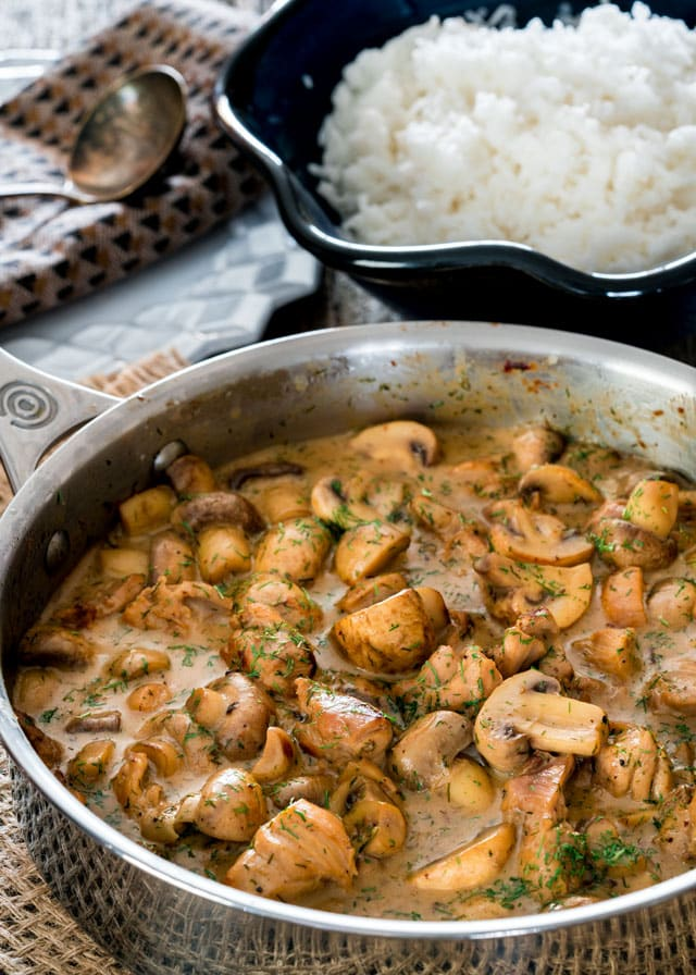 a skillet with a creamy sauce filled with mushrooms and chicken with a big bowl of rice in the background