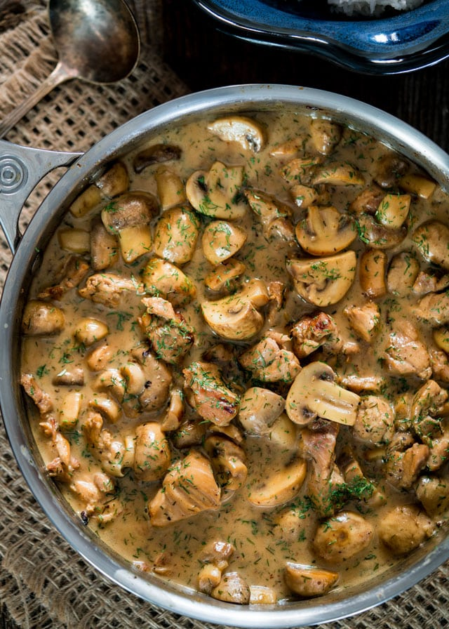 overhead of a skillet full of mushrooms and chicken in a creamy sauce topped with fresh dill