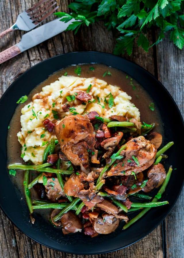 overhead of Coq Au Vin with green beans over mashed potatoes on a black plate