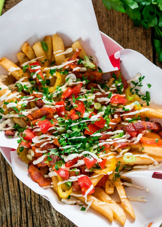 These dirty fries will rock your world! They're loaded with homemade gravy, bacon, banana peppers, green onions, tomatoes, parsley and drizzled with mayonnaise. They're dirty alright, but your belly will thank you!