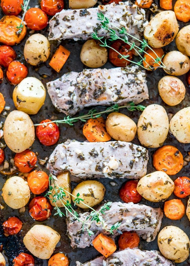 overhead of a sheet pan full of roasted potatoes, carrots, cherry tomatoes, and pork loin.