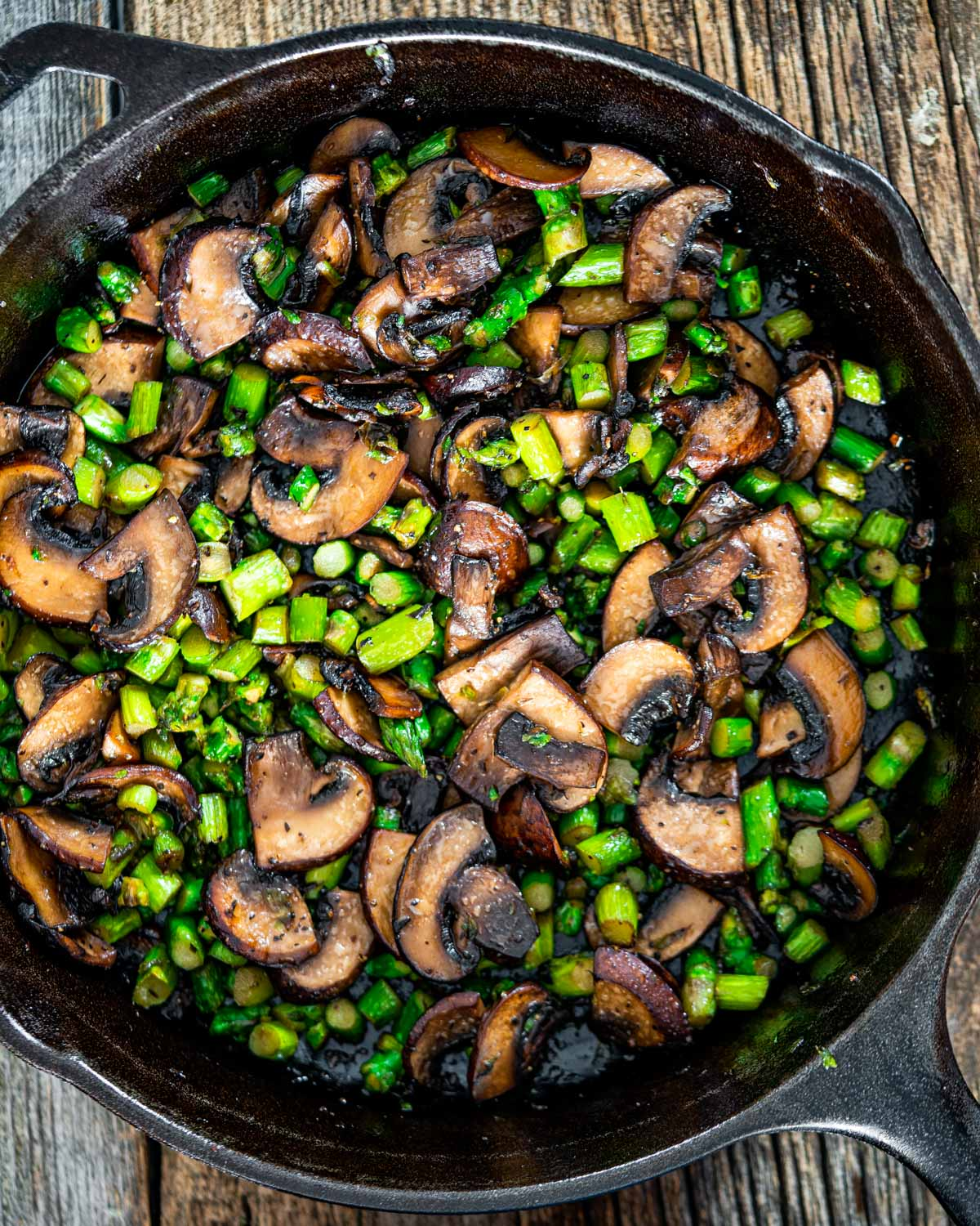 sautéd mushrooms and asparagus in a black skillet