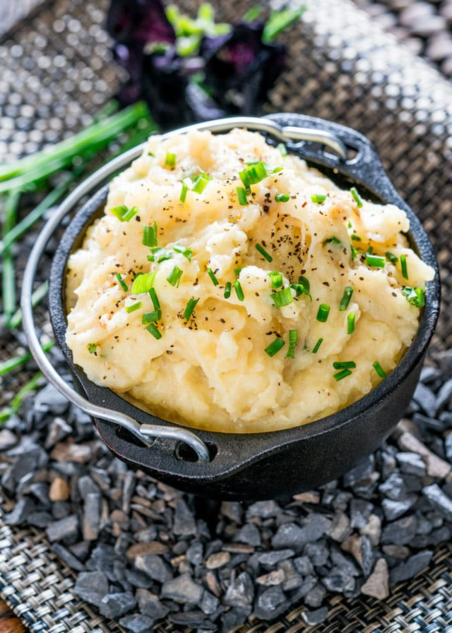 a cast iron bowl with a serving of mashed potatoes topped with chives and pepper