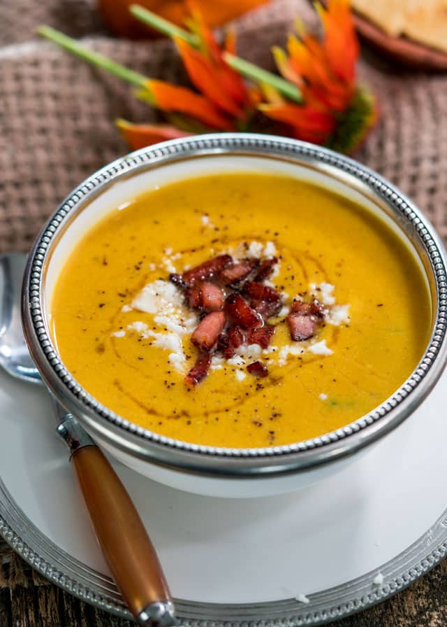 a bowl of butternut squash soup topped with bacon, cheese, pepper, and honey