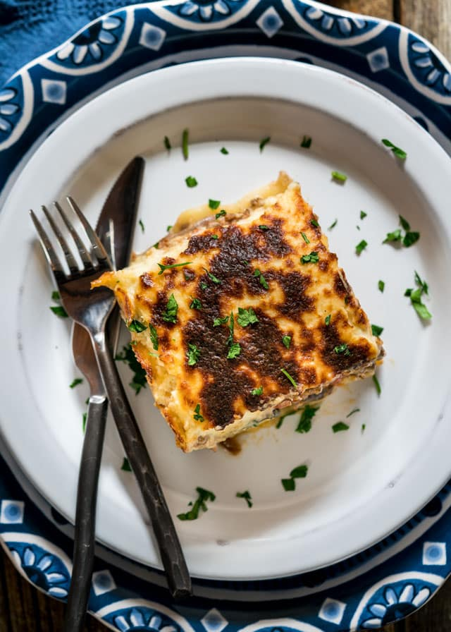 overhead of a plate with a serving of moussaka with a fork and knife