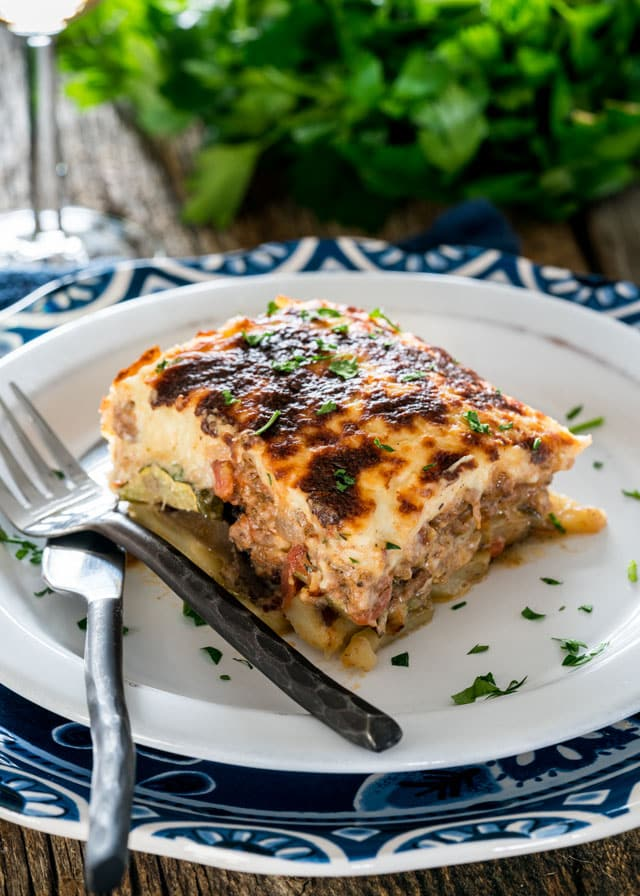 a plate with a serving of moussaka with a fork and knife