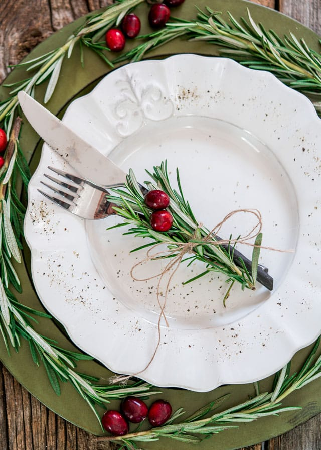 overhead of a plate and cutlery decorated with sprigs of rosemary and fresh cranberries