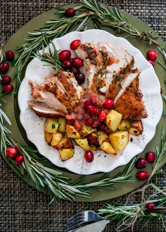 overhead of a plate full of sliced turkey, roasted potatoes, and cranberry sauce decorated with rosemary sprigs and fresh cranberries