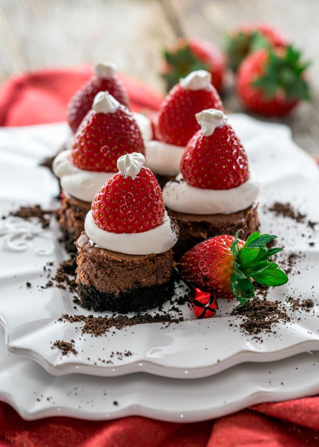 a plate of 5 mini chocolate cheesecakes with whipped cream and strawberry santa hats